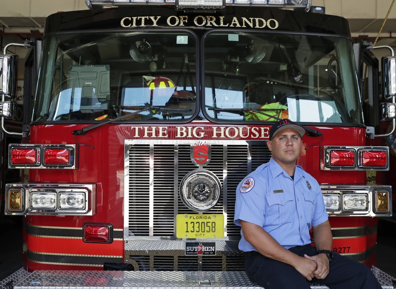 In this Friday, May 24, 2019 photo, Orlando firefighter Jimmy Reyes poses for a portrait next to a firetruck in Orlando, Fla. Reyes enrolled in a program, UCF RESTORES, a clinic at the University of Central Florida that helps first responders, members of the military and some others who've been diagnosed with PTSD. He says he was haunted by the memory of tending to people who'd been shot in 2016 at the Pulse nightclub. The mass shooting left 49 dead. Reyes says the program helped, but he still deals with anxiety.