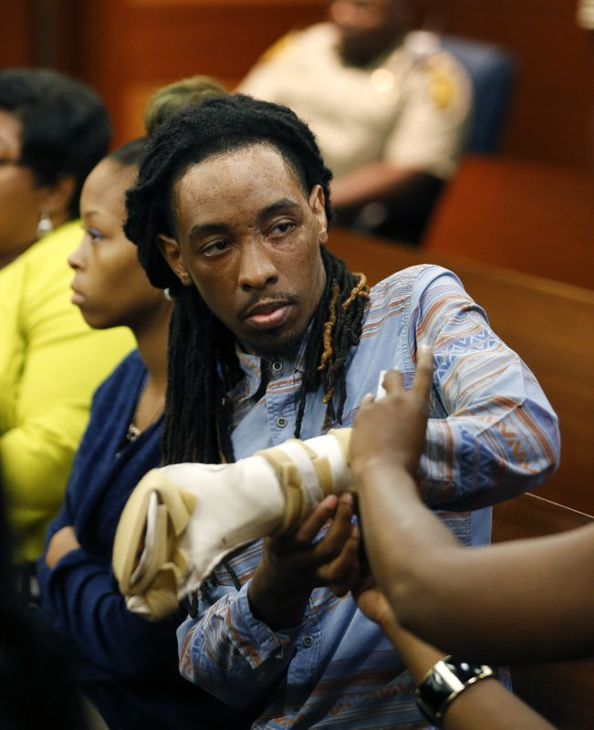 "FILE - In this Aug. 24, 2016 file photo, burn victim Anthony Gooden gets help with his injured hand during a break in the trial for Martin Blackwell in Atlanta. Blackwell, who was convicted of throwing scalding water on a Gooden and his boyfriend while they slept, told one of them to ""get out of my house with all that gay,"" a victim testified, but he couldn't be charged with a hate crime because the state has no such law.  Georgia is one of only four states - along with South Carolina, Wyoming and Arkansas - without an official hate crimes law.   (AP Photo/John Bazemore, File)"