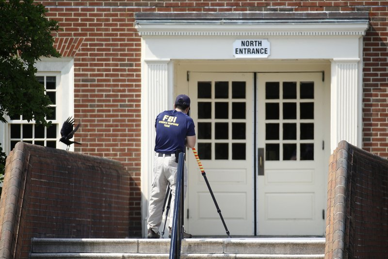 A member of the FBI works outside an entrance to a municipal building that was the scene of a shooting, Sunday, June 2, 2019, in Virginia Beach, Va. DeWayne Craddock, a longtime city employee, opened fire at the building Friday before police shot and killed him, authorities said. (AP Photo/Patrick Semansky)