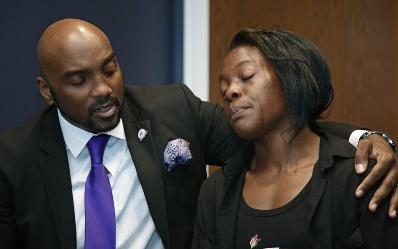 Attorney Damario Solomon-Simmons, left, comforts Olivia Hill, right, as she speaks during an interview in Tulsa, Okla., Friday, May 24, 2019. Three of Hill's children were injured when Hugo, Okla. police officers opened fire on a pickup truck, wounding the three children and a man who authorities say was wanted in a robbery. (AP Photo/Sue Ogrocki)