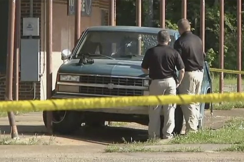 FILE - In this Friday, April 26, 2019 file image made from video provided by KTEN, investigators inspect a pickup truck with bullet holes in its windshield in Hugo, Okla. District Attorney Mark Madoff is reviewing an investigative report to determine if two police officers who shot three children and a robbery suspect at that scene in Hugo should be criminally charged. Hugo police opened fire on a truck April 26, wounding 21-year-old William Devaughn Smith and the children, ages 5, 4 and 1. Madoff says it will take him weeks to review the Oklahoma State Bureau of Investigation report and decide if detectives Billy Jenkins and Chad Allen committed crimes. (KTEN via AP, File)