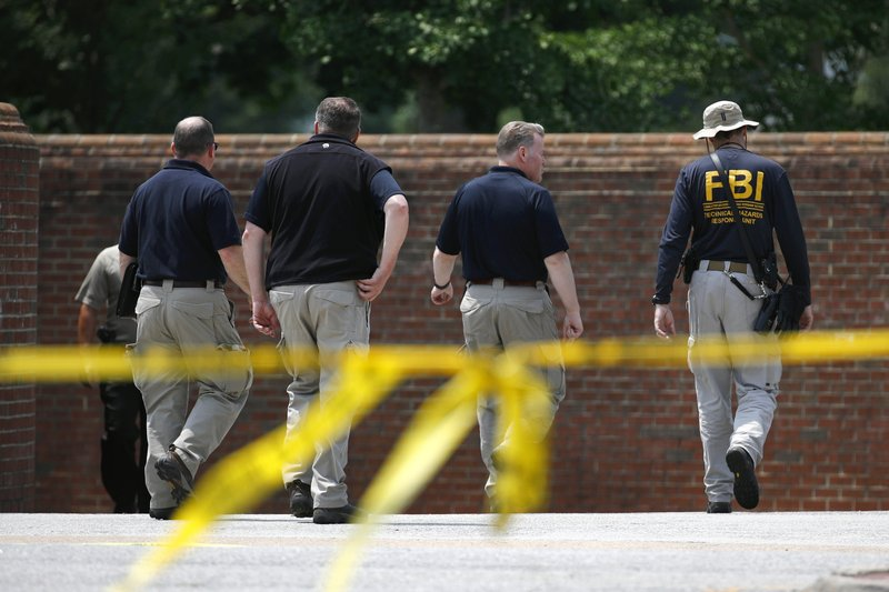 Law enforcement officials walk down a ramp to enter a municipal building that was the scene of a shooting, Sunday, June 2, 2019, in Virginia Beach, Va. DeWayne Craddock, a longtime city employee, opened fire at the building Friday before police shot and killed him, authorities said. (AP Photo/Patrick Semansky)