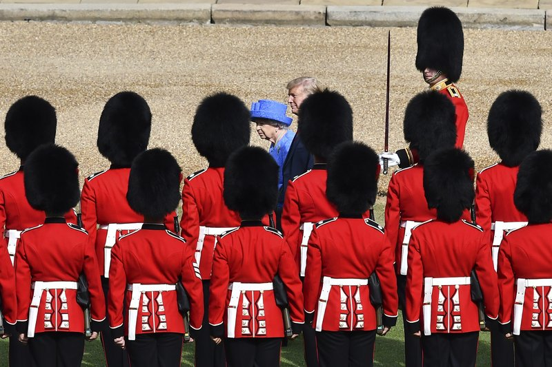 FILE - In this July 13, 2018, file photo, Britain's Queen Elizabeth II and President Donald Trump inspect the Guard of Honour, at Windsor Castle, in Windsor, England. Like a bull who keeps going back to the china shop, Trump is returning to Europe.  (Ben Stansall/Pool Photo via AP)