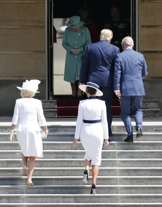 Britain's Queen Elizabeth II waits to greet President Donald Trump and first lady Melania Trump as they walk up the steps with Britain's Prince Charles, right, and Camilla, Duchess of Cornwall, left, during a ceremonial welcome in the garden of Buckingham Palace in London, Monday, June 3, 2019 on the opening day of a three day state visit to Britain. (AP Photo/Frank Augstein)
