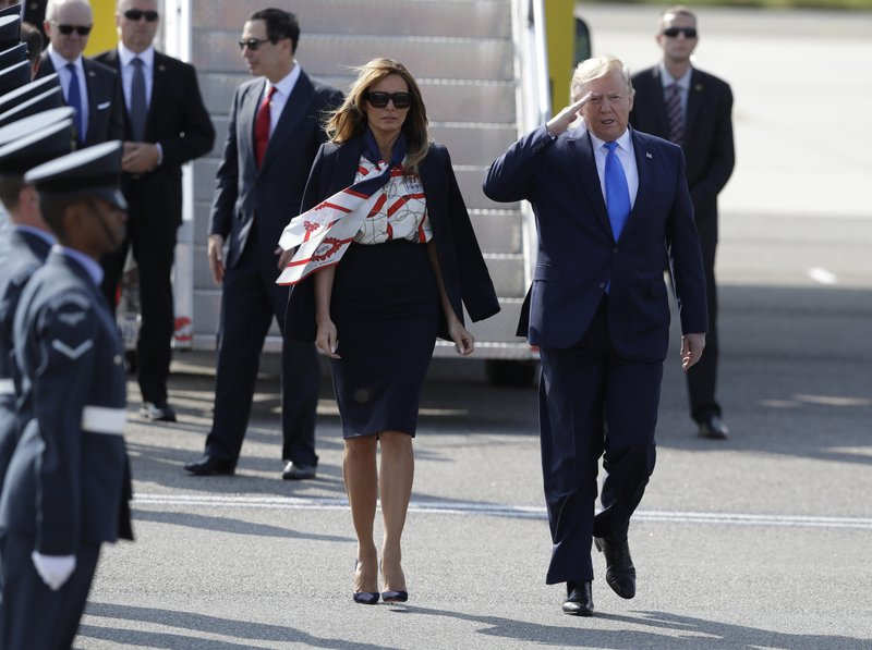 President Donald Trump salutes an honor guard as he and first lady Melania Trump arrive at Stansted Airport in England, Monday, June 3, 2019 at the start of a three day state visit to Britain. (AP Photo/Kirsty Wigglesworth)