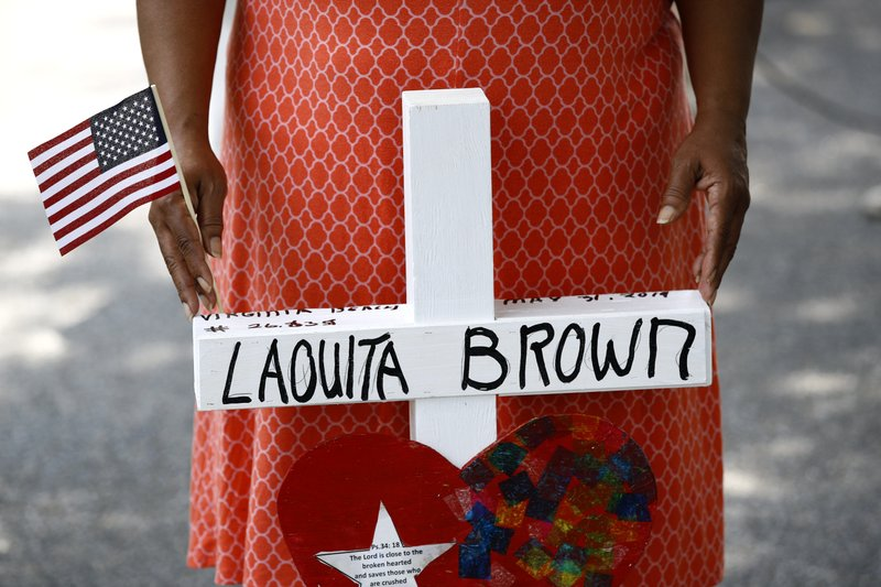 Patricia Olds rests her hands on a cross bearing the name of Olds' coworker, LaQuita Brown, a victim of a mass shooting at a municipal building in Virginia Beach, Va., before carrying the cross to a nearby makeshift memorial, Sunday, June 2, 2019. (AP Photo/Patrick Semansky)