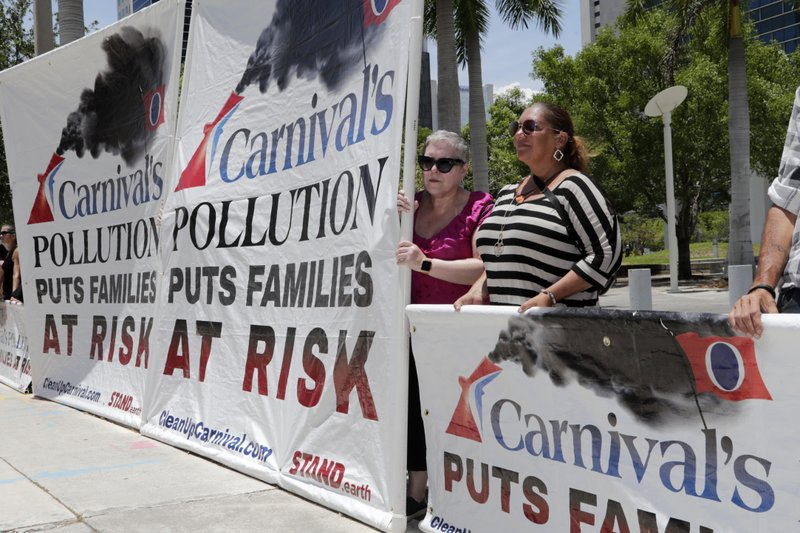 Protestors with Stand.earth hold a banner in opposition to Carnival Corp. outside of federal court, Monday, June 3, 2019, in Miami. Carnival Corp. is in federal court for a hearing on what to do about allegations that it has continued polluting the oceans from some of its cruise ships despite agreeing years ago to stop (AP Photo/Lynne Sladky)