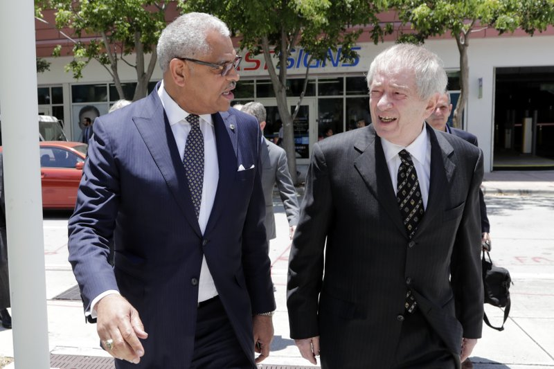 Carnival Corp. President Arnold Donald, left, arrives at federal court, Monday, June 3, 2019, in Miami. Carnival Corp. is in federal court for a hearing on what to do about allegations that it has continued polluting the oceans from some of its cruise ships despite agreeing years ago to stop (AP Photo/Lynne Sladky)