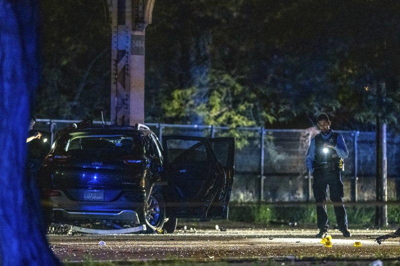 In this Sunday morning, June 2, 2019 photo, Chicago police investigate the scene where multiple people where shot in the East Garfield Park neighborhood of Chicago. Chicago police say dozens of people were shot, several of them fatally, in gun violence over the weekend. (Tyler LaRiviere/Chicago Sun-Times via AP)