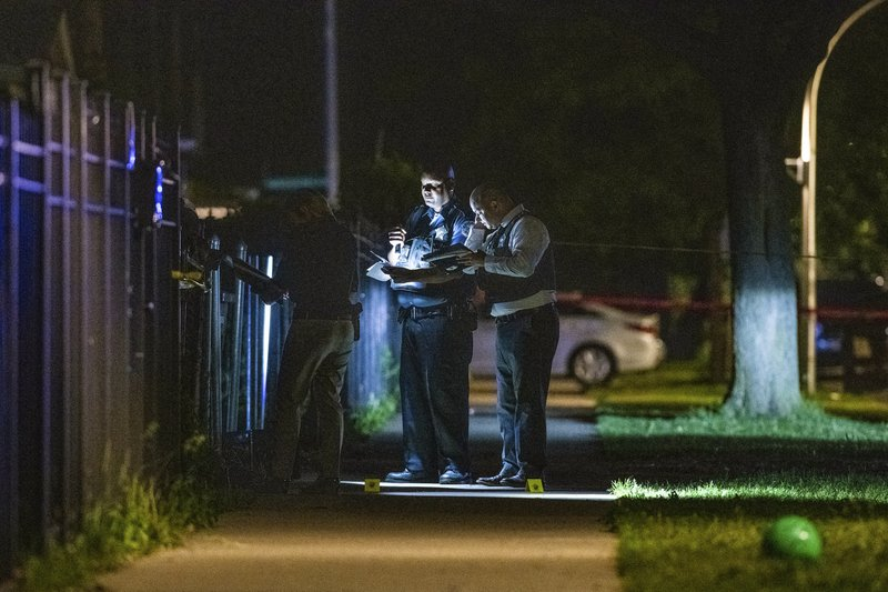 In this Friday night, May 31, 2019 photo, Chicago Police investigate the scene where a person was shot in the West Humboldt Park neighborhood of Chicago. Chicago police say dozens of people were shot, several of them fatally, in gun violence over the weekend. (Tyler LaRiviere/Chicago Sun-Times via AP)