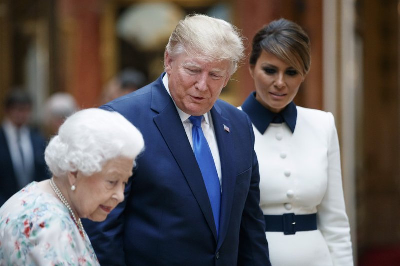 Britain's Queen Elizabeth II speaks to U.S President Donald Trump, centre and first lady Melania as they view U.S memorabilia from the Royal Collection, at Buckingham Palace, London, Monday, June 3, 2019. Trump is on a three-day state visit to Britain. (Tolga Akmen/Pool Photo via AP)