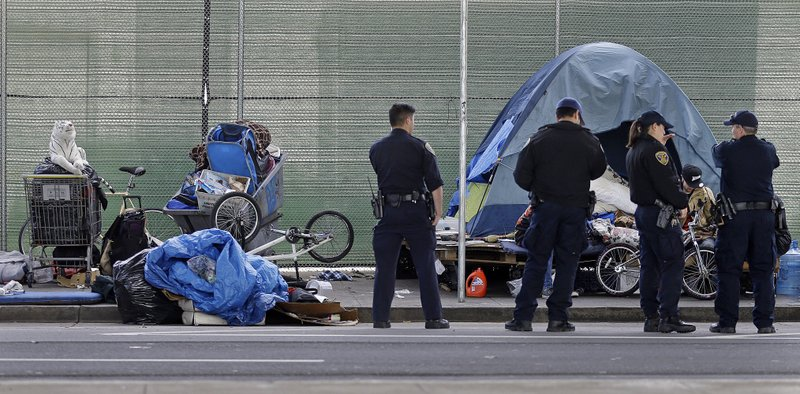 FILE - In this March 1, 2016, file photo, San Francisco police officers wait while homeless people collect their belongings in San Francisco. San Francisco supervisors consider legislation Tuesday, June 4, 2019, allowing the city to force mentally ill drug addicts into housing and treatment for up to a year. Mayor London Breed says it's inhumane to let addicts languish on the streets, but homeless advocates say the measure is extreme and a violation of civil rights.  (AP Photo/Ben Margot, File)
