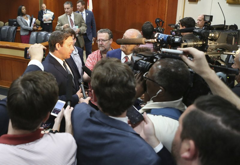 Gov. Ron DeSantis, left, answers questions from the media after the Florida cabinet meeting Tuesday June 4, 2019, in Tallahassee, Fla. (AP Photo/Steve Cannon)