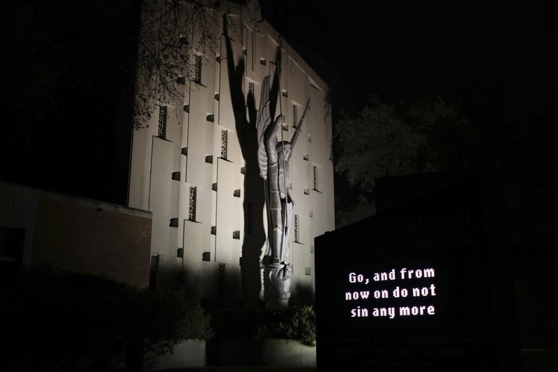 An illuminated sign outside St. Michael Archangel Catholic Church in Houston reads,