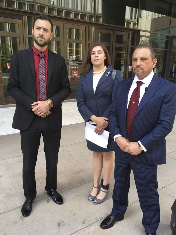 FILE - In this March 29, 2018 file photo, 32-year-old Tahnee Gonzales of Glendale, Arizona, stands next to her attorneys Marc Victor, right, and Andrew Marcantel, left, outside of the courthouse in Phoenix. Gonzales, who was captured on video making derogatory comments about Muslims as she and a friend took Qurans and other items from an Arizona mosque, was sentenced Tuesday, June 4, 2019 to two years of probation for her aggravated criminal damage conviction. . (AP Photo/Jacques Billeaud, File)