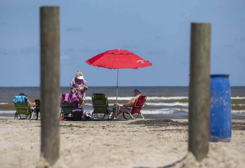 In this June 3, 2019, photo beachgoers relax near the beach access point on Buccaneer Boulevard in the Pirates Beach community on Galveston's west end in Texas. (Stuart Villanueva/The Galveston County Daily News via AP)