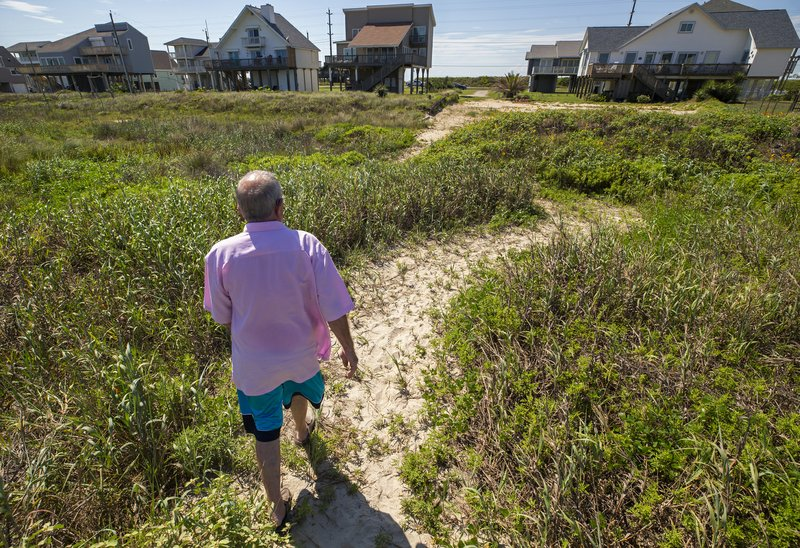 In this June 3, 2019, photo Lafitte's Cove resident Bill Broussard walks up a winding path from the beach to houses in the Sea Isle community on Galveston's west end. (Stuart Villanueva/The Galveston County Daily News via AP)