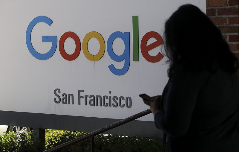 FILE - In this May 1, 2019, file photo, a woman walks past a Google sign in San Francisco. The U.S. Justice Department and the Federal Trade Commission are moving to investigate Google, Facebook, Amazon and Apple over their aggressive business practices, and the House Judiciary Committee has announced an antitrust probe of unidentified technology companies. (AP Photo/Jeff Chiu, File)