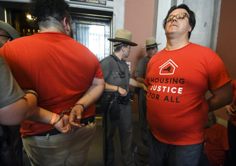 Protesters are arrested by state police as tenants and members of the Upstate Downstate Housing Alliance from across the state, demand New York Gov. Andrew Cuomo and state legislators pass universal rent control legislation that would strengthen and expand tenants rights across the state of New York before rent laws expire on June 15th during a protest rally at the state Capitol Tuesday, June 4, 2019, in Albany, N.Y. (AP Photo/Hans Pennink)