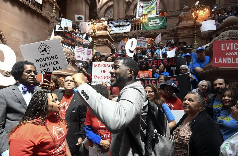 Jumaane Williams, Public Advocate for the City of New York, center, speaks with tenants and members of the Upstate Downstate Housing Alliance from across the state, demanding New York Gov. Andrew Cuomo and state legislators pass universal rent control legislation that would strengthen and expand tenants rights across the state of New York before rent laws expire on June 15th during a protest rally at the state Capitol Tuesday, June 4, 2019, in Albany, N.Y. (AP Photo/Hans Pennink)