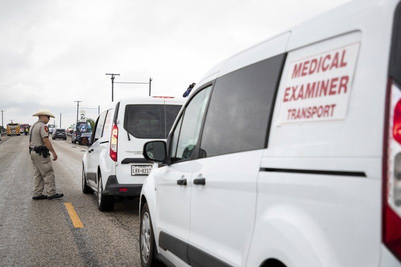 The medical examiners office arrives as law enforcement investigate a fatal wreck that left six migrants dead and several others injured outside Robstown, Texas on Wednesday, June 5, 2019. (Courtney Sacco/Corpus Christi Caller-Times via AP)