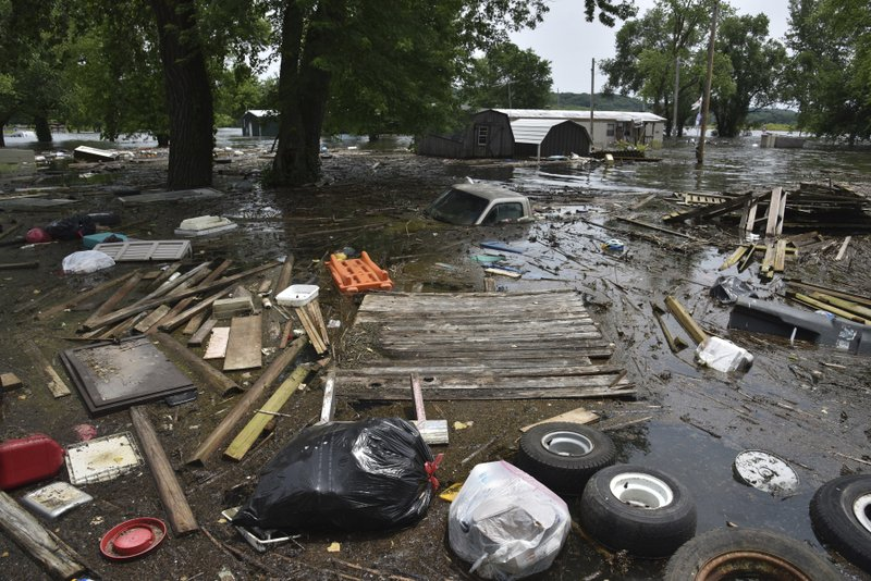 In this Monday, June 3, 2019 photo, debris floats in floodwaters near the confluence of Perche Creek and the Missouri River in the central-Missouri town of McBaine, Mo. (Kate Seaman/Missourian via AP)