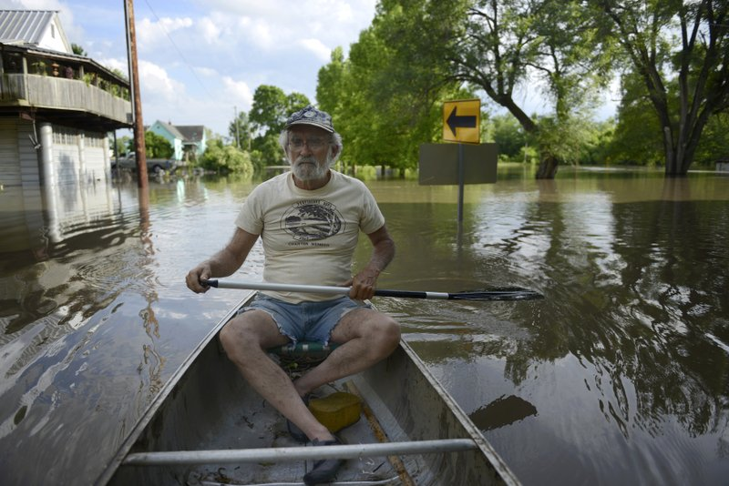 In this Tuesday, June 4, 2019 photo, Doug Elley rows his canoe through floodwaters down the center of town in Lupus, Mo.. Elley is a former mayor of the town. He now owns and manages the Lupus General Store. Elley and other central Missourians see the recent floods as reminiscent of the Great Flood of 1993.