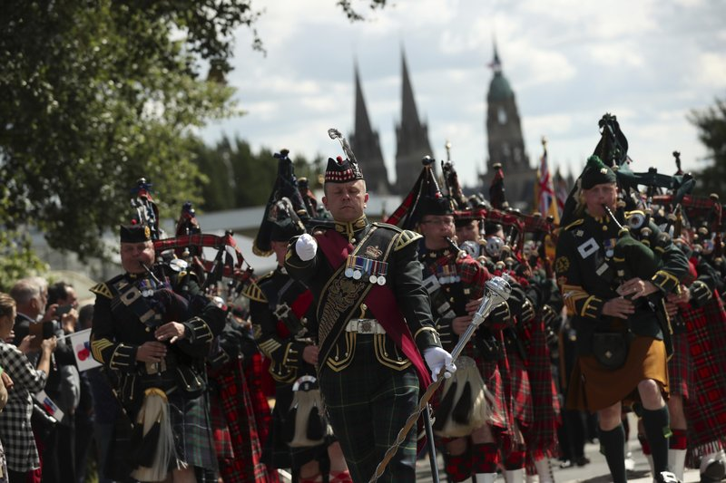 Bagpipers lead a procession of British World War II veterans to the Bayeux War Cemetery for a ceremony to mark the 75th anniversary of D-Day in Bayeux, Normandy, France, Thursday, June 6, 2019. World leaders gathered Thursday in France to mark the 75th anniversary of the D-Day landings.(AP Photo/Francisco Seco)