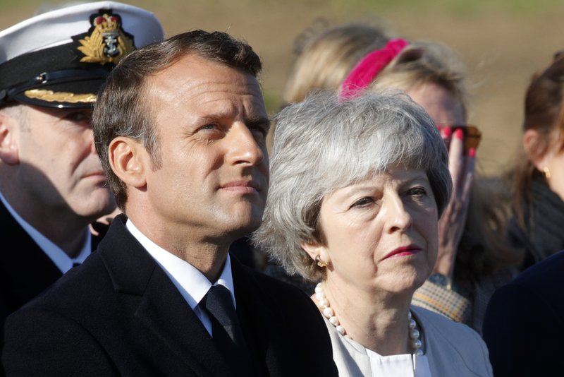 British Prime Minister Theresa May and French President Emmanuel Macron attend a Franco-British ceremony to mark the 75th anniversary of D-Day landings and laying the first stone of a British memorial at Ver-Sur-Mer, Normandy, Thursday, June 6, 2019.(Philippe Wojazer/Pool via AP)
