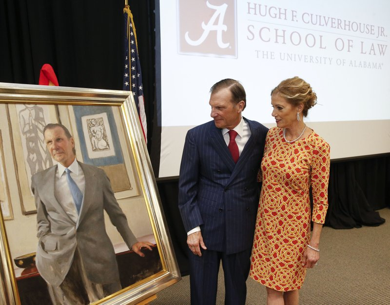 In this Sept. 20, 2018, photo, Hugh F. Culverhouse Jr. and his wife, Eliza, look at a portrait of him that will hang in the  University of Alabama law school in Tuscaloosa, Ala. The university appears poised to reject a $26.5 million pledge by Culverhouse, who recently called on students to boycott the university over the state's new abortion ban. (Gary Cosby Jr./The Tuscaloosa News via AP)