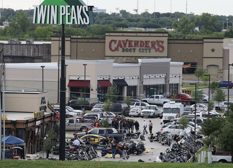 FILE - In this May 17, 2015 file photo, authorities investigate a shooting in the parking lot of Twin Peaks restaurant in Waco, Texas. An attorney for six men arrested after the 2015 shootout between rival biker gangs that left nine people dead and at least 20 injured asked a district court judge Wednesday, June 5, 2019, to assign a special master to supervise the return of items seized from the nearly 200 detained bikers. (AP Photo/Jerry Larson, File)