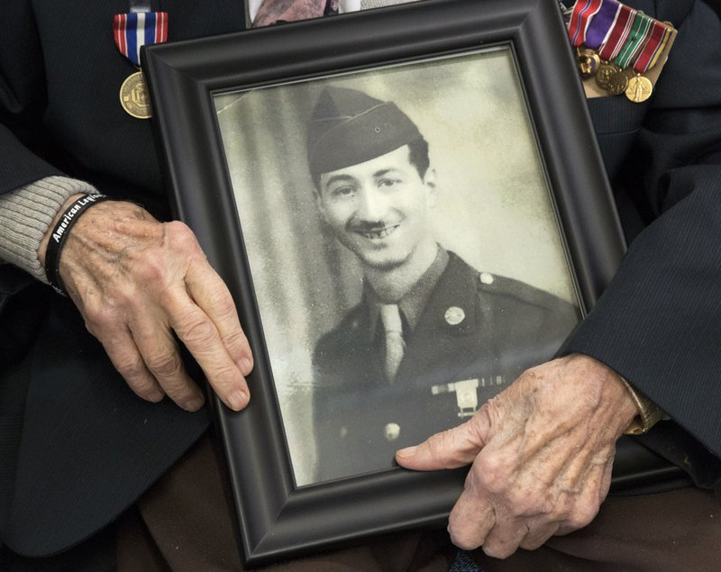 D-Day veteran Frank De Pergola, 96, poses with his wartime service photo prior to a 75th anniversary ceremony, Thursday, June 6, 2019, at the Long Island State Veterans Home in Stony Brook, N.Y. DePergola served as an army combat infantryman in Normandy, and then in the Battle of the Bulge. (AP Photo/Mark Lennihan)