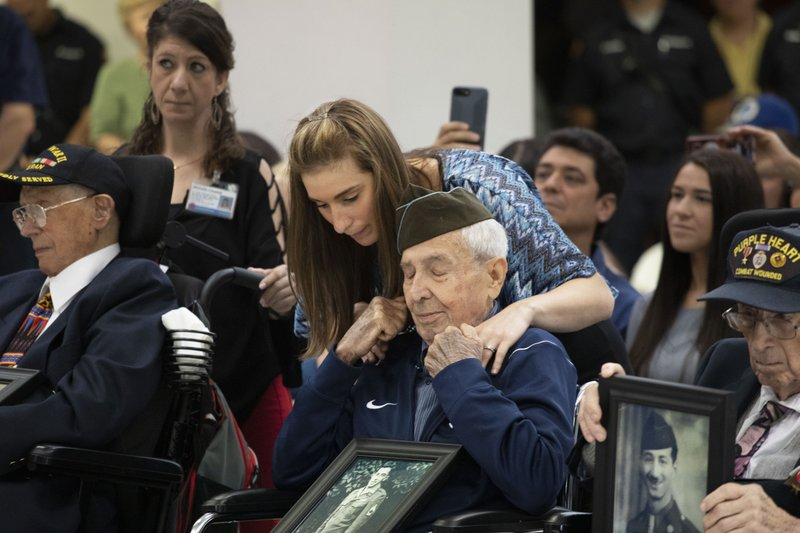 Philip Di Marco, center, a D-Day veteran, is comforted by Samantha Calandrino, a volunteer coordinator with the Long Island State Veterans Home, during a 75th anniversary ceremony, Thursday, June 6, 2019, in Stony Brook, N.Y.  Di Marco was part of the First Wave of soldiers storming the beach at Normandy. (AP Photo/Mark Lennihan)