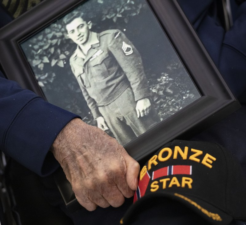 D-Day veteran Philip Di Marco holds his wartime service photo during a 75th anniversary ceremony at the Long Island State Veterans Home, Thursday, June 6, 2019, in Stony Brook, N.Y.  Di Marco was part of the First Wave of soldiers storming the beach at Normandy. (AP Photo/Mark Lennihan)