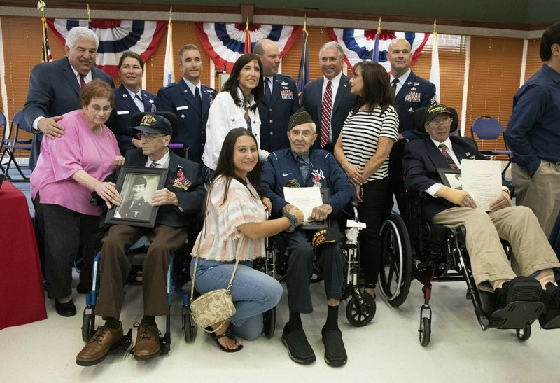 D-Day veterans Frank De Pergola, left, Philip Di Marco, center, and Charles Cino, right, are joined by family and members of the U.S. Army during a 75th anniversary ceremony at the Long Island State Veterans Home, Thursday, June 6, 2019, in Stony Brook, N.Y. (AP Photo/Mark Lennihan)