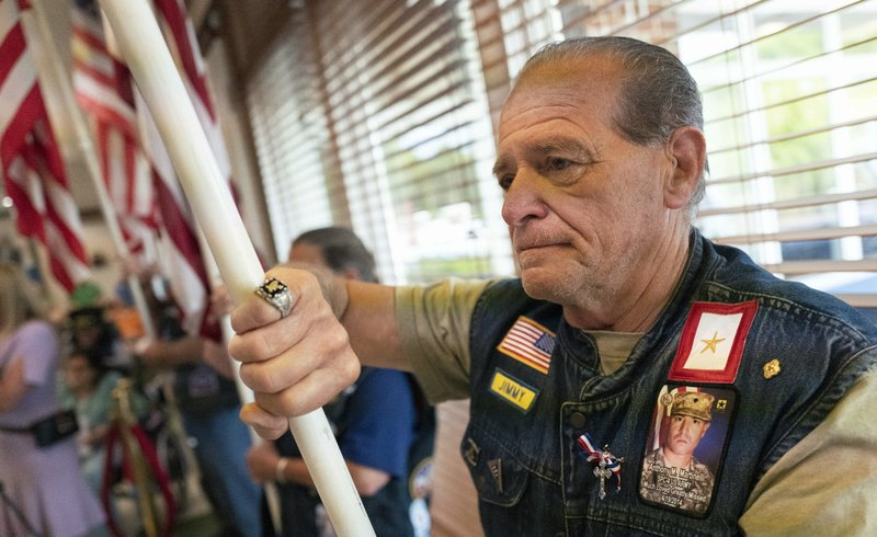 Jim Martinelli is part of the color guard during a 75th Anniversary of D-Day ceremony, Thursday, June 6, 2019, at the Long Island State Veterans Home in Stony Brook, N.Y. Martinelli, of Lindenhurst, N.Y., is wearing a photo of his son, Anthony Martinelli, who was killed in Afghanistan in 2014. (AP Photo/Mark Lennihan)