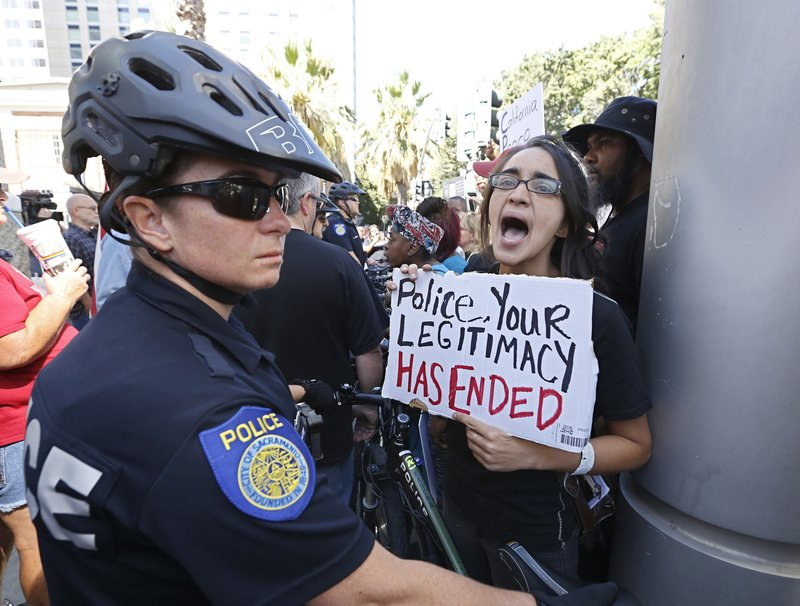 FILE - In this Sept. 18, 2018 file photo, Sacramento Police block protesters outside the Sacramento Convention Center, where a law enforcement conference is being held in Sacramento, Calif. Organizers of a pride parade in California reversed course and said uniformed police officers will be welcome at the festivities. The announcement came Thursday, June 6, 2019, after the Sacramento LGBT Community Center and Sacramento Police Department created a partnership that will include a police liaison and training for new officers with discussions about bias. (AP Photo/Rich Pedroncelli, File)