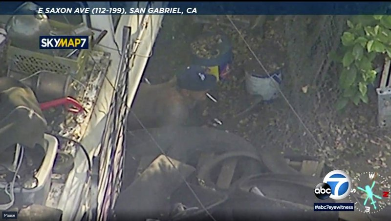 In this photo made from video provided by KABC-TV, a shirtless man crawls out from under a vehicle with a cigarette in his mouth at a property in San Gabriel, Calif. The gunman held police at bay for hours Thursday, set fire to several homes and launched fireworks at surrounding SWAT team members before he charged out of a home with a shotgun and was shot dead, authorities said. (KABC-TV via AP)