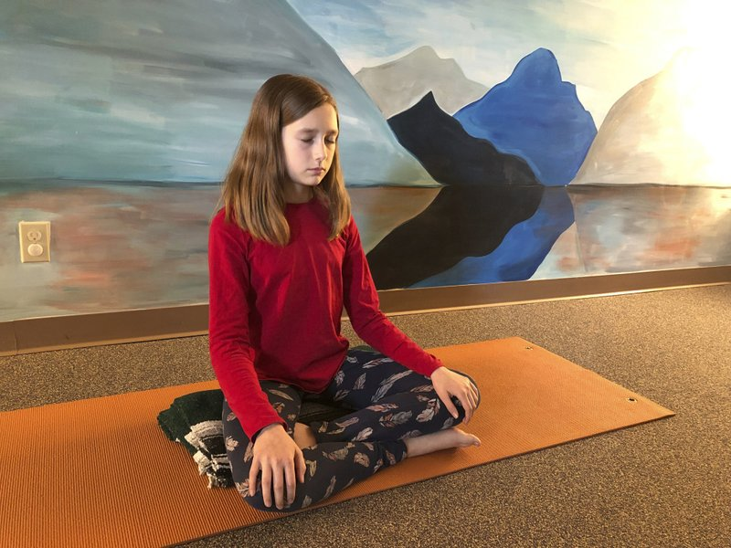 In this May 14, 2019 photo, Aeva Schifferli, 12, demonstrates a stress-relieving breathing exercise at her mother's yoga studio in East Aurora, N.Y. Her mother Erin Schifferli plans to wait until Aeva is 16 before getting her a cellphone out of concern that the technology, especially social media, is contributing to rising levels of anxiety and depression among teenagers. (AP Photo/Carolyn Thompson)
