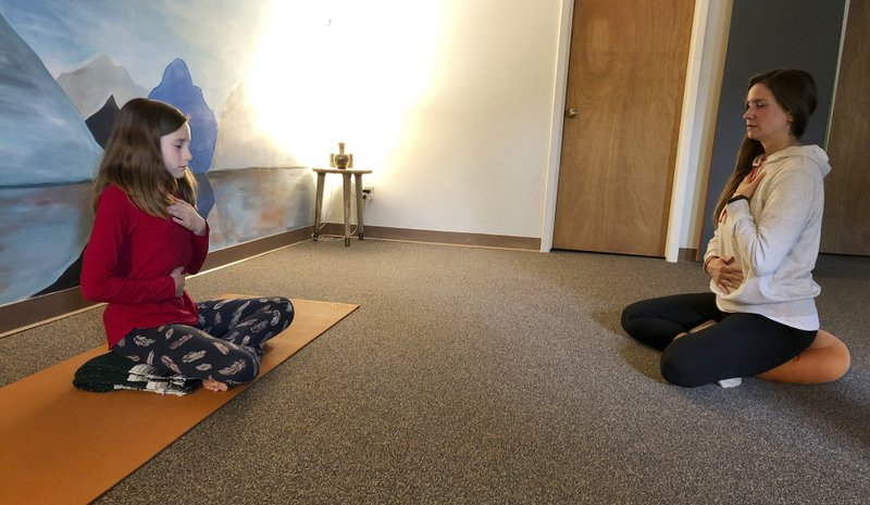 In this May 14, 2019 photo, yoga instructor Erin Schifferli and her 12-year-old daughter, Aeva, demonstrate a stress-relieving breathing exercise in her studio in East Aurora, N.Y. Schifferli plans to wait until Aeva is 16 before getting her a cellphone out of concern that the technology, especially social media, is contributing to rising levels of anxiety and depression among teenagers. (AP Photo/Carolyn Thompson)