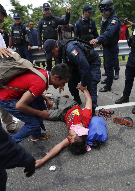 A migrant is tended by a Federal Police officer and a fellow migrant after he collapsed when an attempt was made to detain him by Mexican immigration authorities during a raid on a migrant caravan that had earlier crossed the Mexico - Guatemala border, near Metapa, Chiapas state, Mexico, Wednesday, June 5, 2019. (AP Photo/Marco Ugarte)