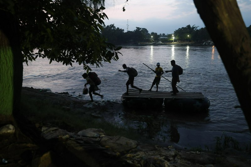 Migrants on rafts reach the Mexico shore after crossing the Suchiate river on the Guatemala – Mexico border, near Ciudad Hidalgo, Mexico, Wednesday, June 5, 2019. Hundreds more Central American migrants have crossed into Mexico from Guatemala, and a group of about 1,000 have started walking en mass to the north. (AP Photo/Marco Ugarte)