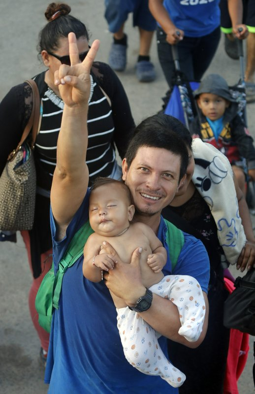 A migrant father carries his child as hundreds of Central American migrants walk on the highway, after crossing the Guatemala – Mexico border, near Ciudad Hidalgo, Mexico, Wednesday, June 5, 2019. State and local police provided a security escort to the migrants as they walked along a highway leading from the border to the first major city in Mexico, Tapachula. (AP Photo/Marco Ugarte)