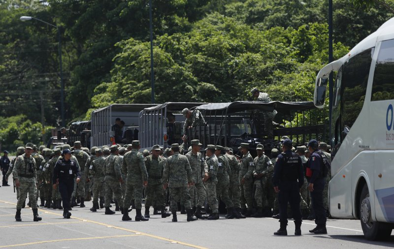 Police officers, Marines, Military Police and immigration officials form up on the highway, in Metapa, Chiapas state, Mexico, Wednesday, June 5, 2019. The law enforcement group arrived at the area to intercept a caravan of migrants that had earlier crossed the Mexico – Guatemala border. (AP Photo/Marco Ugarte)