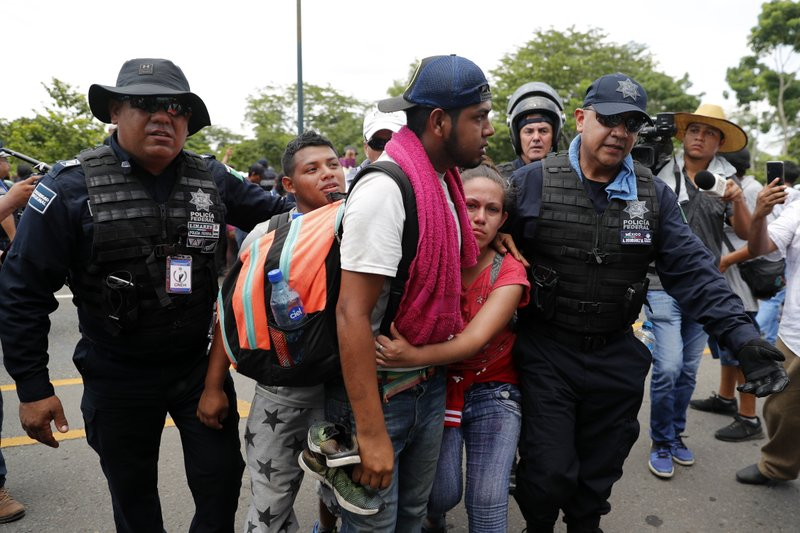 Migrants are detained by Mexican immigration authorities during a raid on a migrant caravan that had earlier crossed the Mexico - Guatemala border, near Metapa, Chiapas state, Mexico, Wednesday, June 5, 2019. (AP Photo/Marco Ugarte)