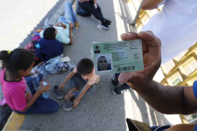 Honduran migrant Jose Maria Dubon Gutierrez shows his legal permission to stay in Mexico's southern states as he waits with his family, behind, at a border crossing between Guatemala and Mexico for his family's turn to show Mexican immigration officers their documents near Ciudad Hidalgo, Mexico, Thursday, June 6, 2019. While Mexico has been discouraging the kind of large-scale caravans that it saw in 2018 and the first few months of 2019, Trump's administration wants Mexico to do more to curb migrants from reaching the U.S. border. (AP Photo/Marco Ugarte)