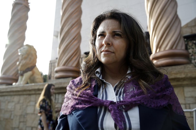 Bibiana Ochoa, of Salt Lake City, a member of La Luz del Mundo church, stands outside one of the church's branches before the start of a service Thursday, June 6, 2019, in Los Angeles. California's top prosecutor said Thursday that he believes there are more victims of child sex abuse than those listed in charges against the leader of Mexico-based megachurch La Luz del Mundo and several followers. (AP Photo/Marcio Jose Sanchez)