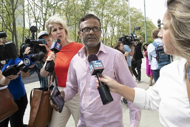Ashiqul Alam 's father is surrounded by reporters as she leaves federal court in Brooklyn, Friday, June 7, 2019, in New York. Alam was arrested Thursday after arranging through an undercover agent to buy a pair of semiautomatic pistols with obliterated serial numbers, prosecutors said. (AP Photo/Mary Altaffer)