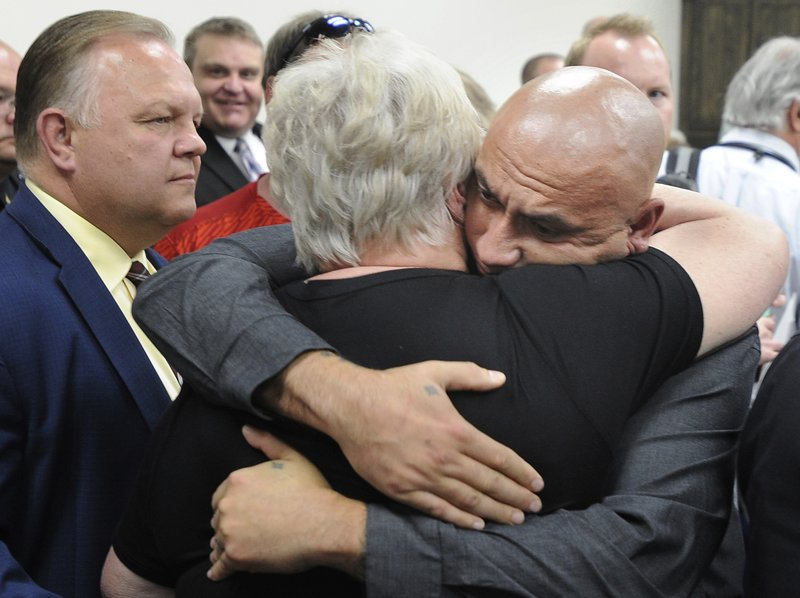 In this May 16, 2019 photo, Christopher Tapp hugs Carol Dodge at the conclusion of a press conference where the Idaho Falls Police announced that Brian Leigh Dripps had been arrested for the murder of Carol's daughter Angie in 1996, in Idaho Falls, Idaho. Detectives identified Dripps using GEDmatch. Carol's son Brent is pictured left. (Monte LaOrange/The Idaho Post-Register via AP)
