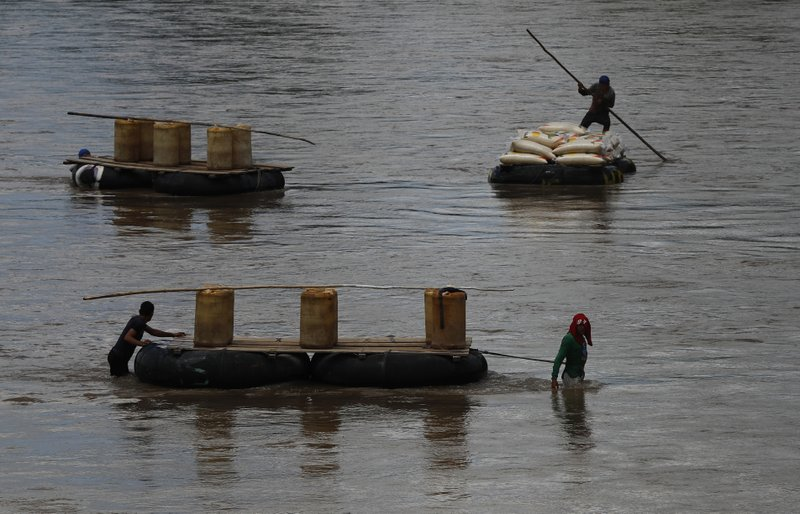 Men use rafts to transport black-market gasoline across the Suchiate River from Guatemala to Mexico, as one pushes sacks of corn in the opposite direction to Guatemala, near Ciudad Hidalgo, Mexico, Thursday, June 6, 2019. U.S. President Donald Trump has pledged to impose 5% tariffs on Mexican products unless Mexico country prevents Central American migrants from traveling through its territory. Some migrants pay raft operators in order to avoid swimming or going through the official border crossing. (AP Photo/Marco Ugarte)